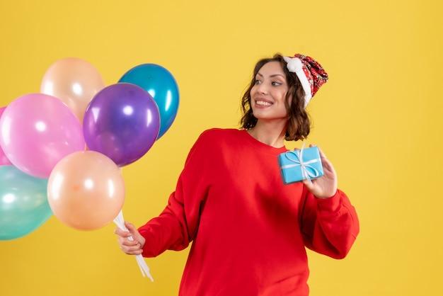 Widok z przodu młoda kobieta trzyma balony i mały prezent na żółte święta bożego narodzenia nowy rok emocje kolor kobieta