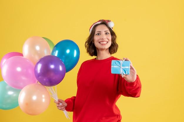Widok z przodu młoda kobieta trzyma balony i mały prezent na żółty boże narodzenie wakacje nowy rok emocja kolor kobieta