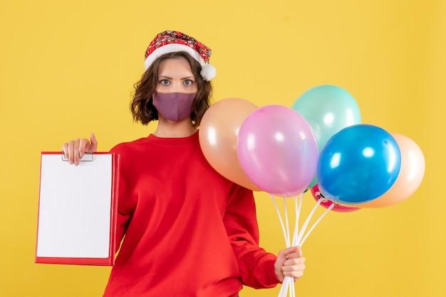 Widok z przodu młoda kobieta trzyma balony i plik notatki na żółtym wirusie covid party emocja nowy rok kolor kobieta