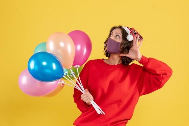 Widok z przodu młoda kobieta trzyma balony w masce nasłuchując na żółtym uroczystość party emocja nowy rok kolor kobieta
