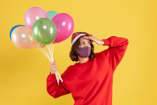 Widok z przodu młoda kobieta trzyma balony w sterylnej masce na jasnożółtym