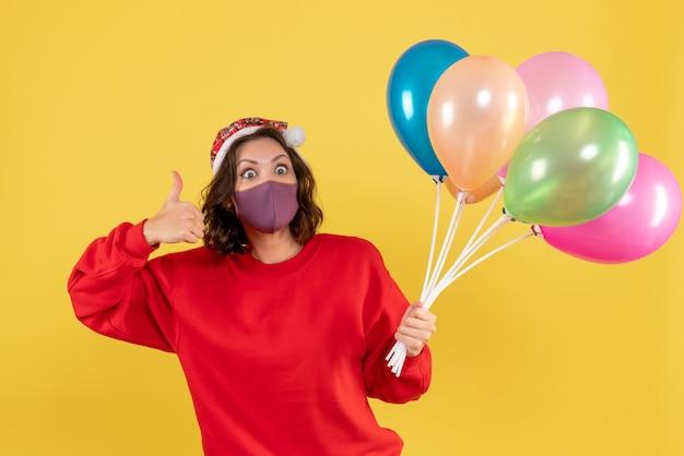 Widok z przodu młoda kobieta trzyma balony w sterylnej masce na żółto