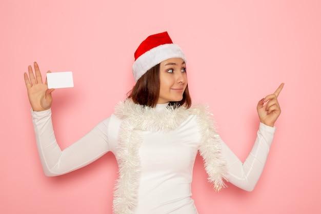 Widok z przodu młoda kobieta trzyma białą kartę bankową na różowej ścianie boże narodzenie nowy rok moda kolor wakacje pieniądze