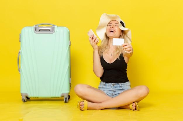 Widok z przodu młoda kobieta trzyma białą kartę i korzysta z telefonu