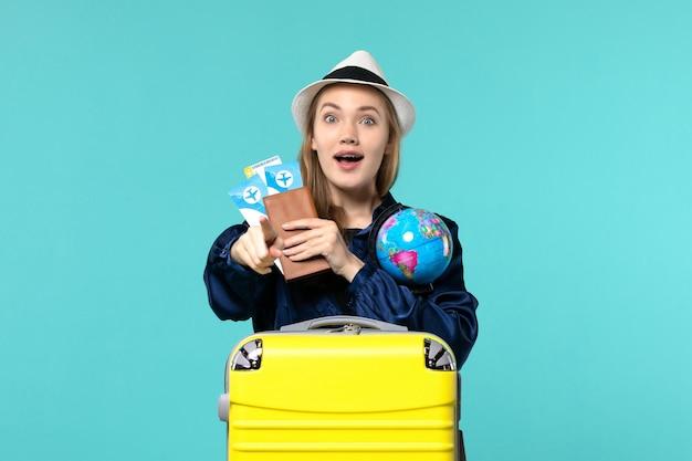 Widok z przodu młoda kobieta trzyma bilety i kula ziemska na jasnoniebieskim tle samolot podróż morska podróż wakacje