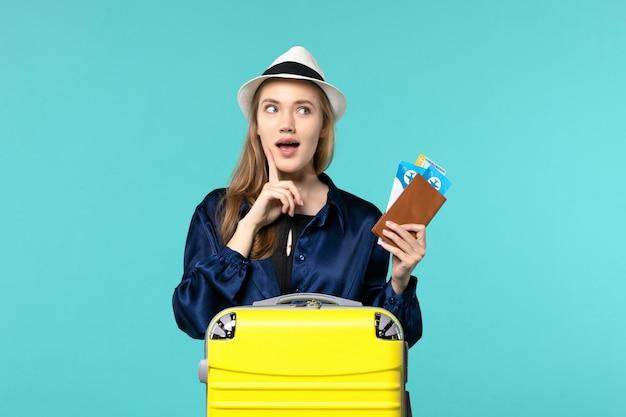 Widok z przodu młoda kobieta trzyma bilety i przygotowuje się do podróży na jasnoniebieskim tle podróż rejs samolot podróż morska wakacje