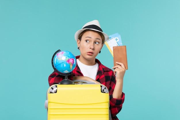 Widok z przodu młoda kobieta trzyma bilety na niebieskiej przestrzeni