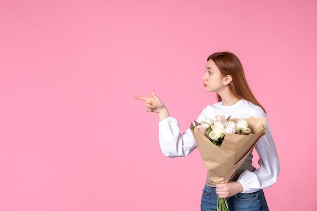 Widok z przodu młoda kobieta trzyma bukiet pięknych róż na pinks