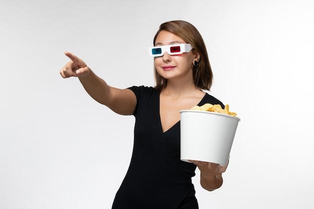 Widok z przodu młoda kobieta trzyma chipsy d okulary przeciwsłoneczne i ogląda film na białej powierzchni