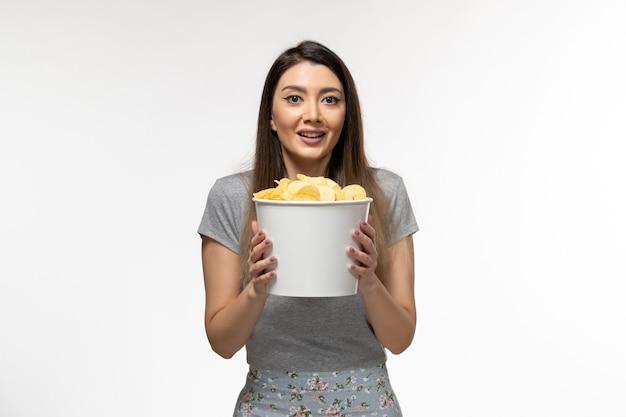 Widok z przodu młoda kobieta trzyma chipsy ziemniaczane i ogląda film na białej powierzchni