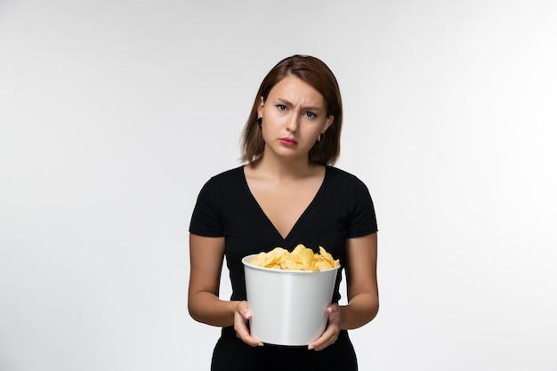 Widok z przodu młoda kobieta trzyma chipsy ziemniaczane i ogląda film na białym biurku