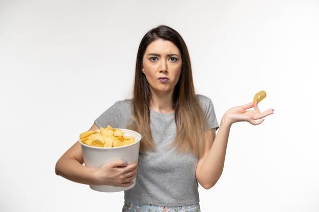Widok z przodu młoda kobieta trzyma chipsy ziemniaczane podczas oglądania filmu na białej powierzchni