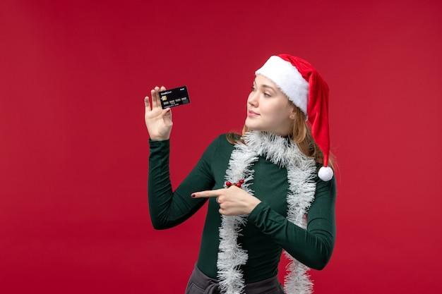Widok z przodu młoda kobieta trzyma czarną kartę bankową na czerwonym tle