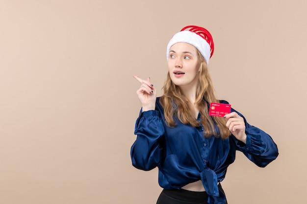 Widok z przodu młoda kobieta trzyma czerwoną kartę bankową na różowym tle pieniądze wakacje zdjęcie nowy rok boże narodzenie emocje wolne miejsce