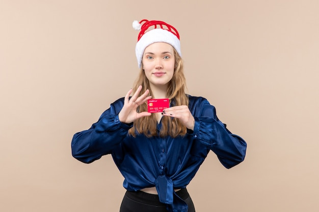 Widok z przodu młoda kobieta trzyma czerwoną kartę bankową na różowym tle wakacje zdjęcie nowy rok emocje pieniądze świąteczne