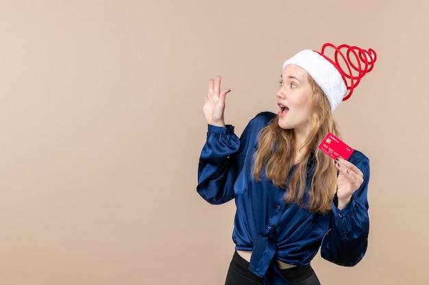 Widok z przodu młoda kobieta trzyma czerwoną kartę bankową na różowym tle wakacje zdjęcie nowy rok xmas pieniądze emocje wolne miejsce