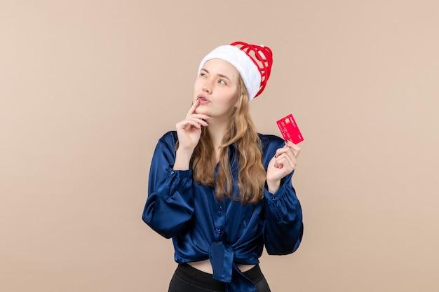 Widok z przodu młoda kobieta trzyma czerwoną kartę bankową na różowym tle xmas pieniędzy zdjęcie wakacje nowy rok emocji