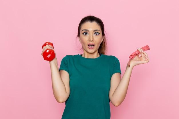 Widok z przodu młoda kobieta trzyma czerwone hantle na jasnoróżowej ścianie sportowiec ćwiczenia zdrowotne ćwiczenia