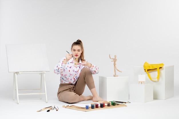 Widok z przodu młoda kobieta trzyma farby do rysowania na białym tle