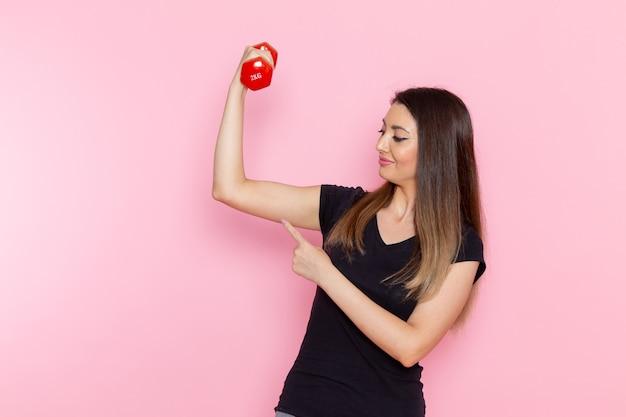 Widok z przodu młoda kobieta trzyma hantle na jasnoróżowym biurku sportowiec ćwiczenia zdrowotne