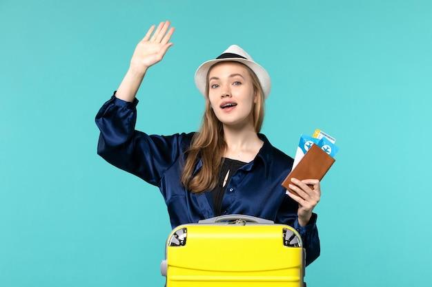 Widok z przodu młoda kobieta trzyma jej bilety i przygotowuje się do podróży na jasnoniebieskim tle podróż rejs samolot podróż morska wakacje