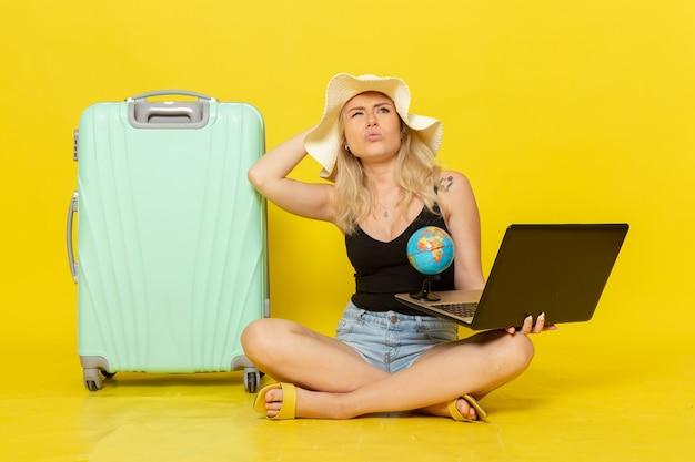 Widok z przodu młoda kobieta trzyma jej laptopa i kulę ziemską
