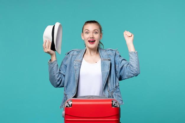 Widok z przodu młoda kobieta trzyma kapelusz i przygotowuje się do podróży na jasnoniebieskiej przestrzeni