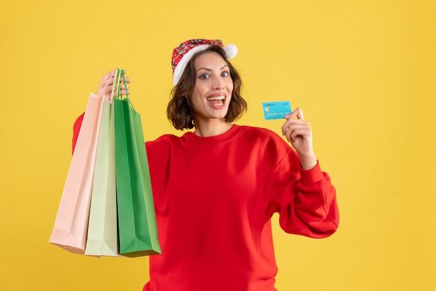 Widok z przodu młoda kobieta trzyma kartę bankową i pakiety na żółto
