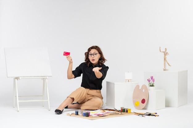 Widok z przodu młoda kobieta trzyma kartę bankową na białym tle