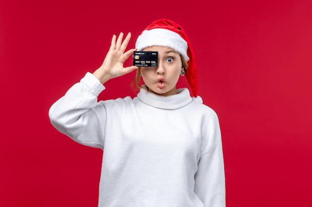 Widok z przodu młoda kobieta trzyma kartę bankową na czerwonej podłodze czerwone święto pieniędzy na boże narodzenie