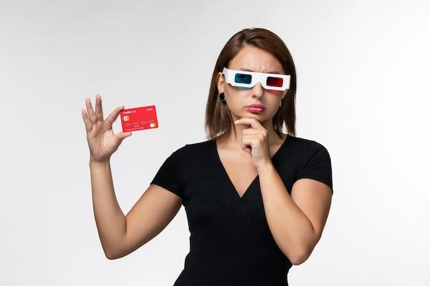 Widok z przodu młoda kobieta trzyma kartę bankową w d okulary przeciwsłoneczne i myśli na białej powierzchni