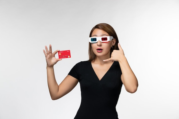 Widok z przodu młoda kobieta trzyma kartę bankową w d okulary przeciwsłoneczne na jasnobiałej powierzchni