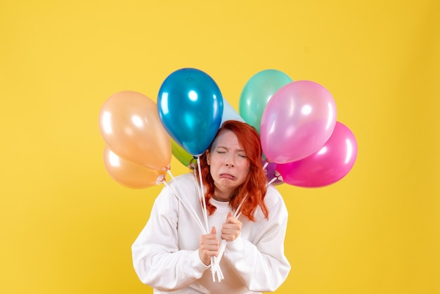 Widok z przodu młoda kobieta trzyma kolorowe balony i fałszywy płacz na żółto