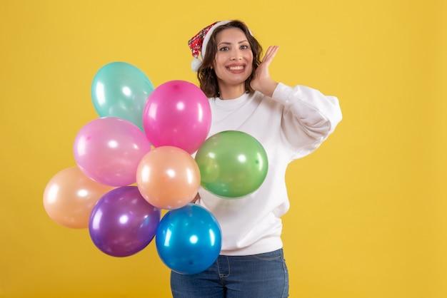 Widok z przodu młoda kobieta trzyma kolorowe balony na żółto