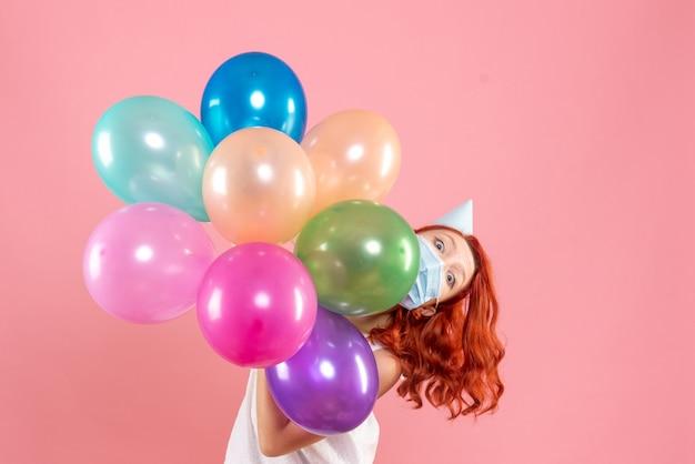 Widok z przodu młoda kobieta trzyma kolorowe balony w masce na jasnoróżowym