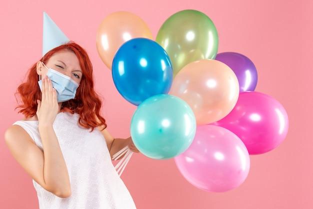 Widok z przodu młoda kobieta trzyma kolorowe balony w masce na różowo