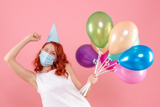 Widok z przodu młoda kobieta trzyma kolorowe balony w sterylnej masce na różowo