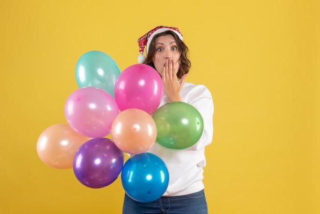 Widok z przodu młoda kobieta trzyma kolorowe balony z zdziwioną twarzą na żółto