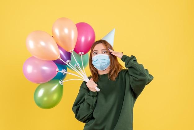 Widok z przodu młoda kobieta trzyma kolorowe balony