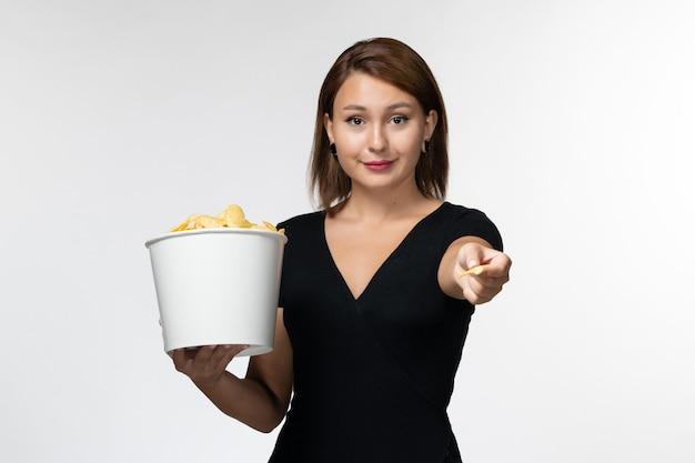 Widok z przodu młoda kobieta trzyma kosz z chipsami ziemniaczanymi i je na jasnej białej powierzchni