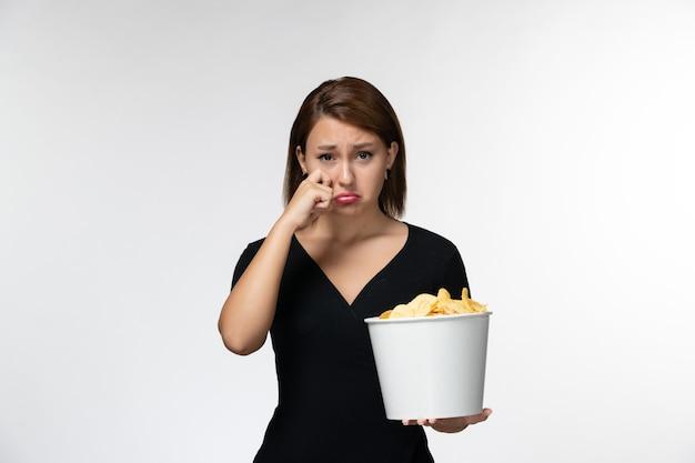 Widok z przodu młoda kobieta trzyma kosz z chipsami ziemniaczanymi oglądając film płaczący na białej powierzchni