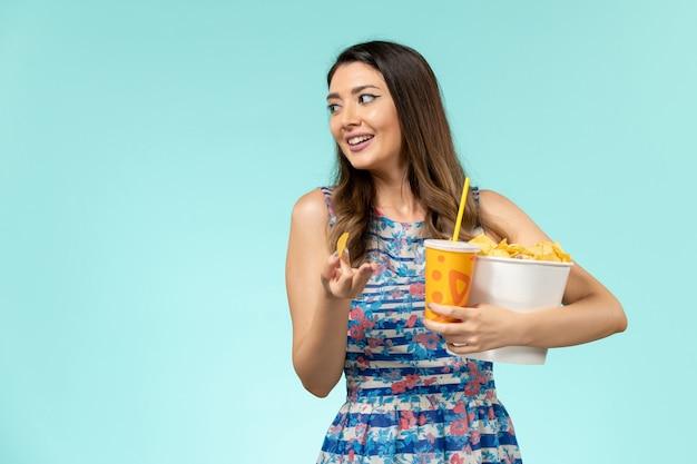 Widok z przodu młoda kobieta trzyma kosz z frytkami i napojem na niebieskiej powierzchni