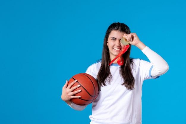 Widok z przodu młoda kobieta trzyma koszykówkę na niebieskiej ścianie