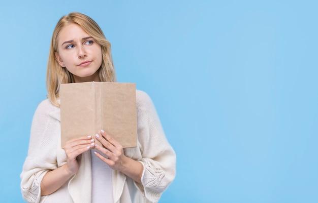 Widok z przodu młoda kobieta trzyma książkę