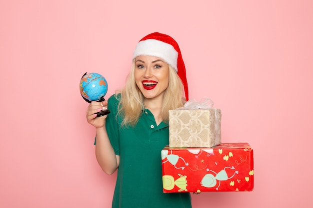 Widok z przodu młoda kobieta trzyma kulę ziemską i prezenty świąteczne na różowej ścianie zdjęcie model kobieta boże narodzenie nowy rok kolor wakacje