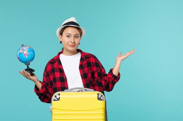 Widok z przodu młoda kobieta trzyma małą kulę ziemską na jasnoniebieskiej przestrzeni