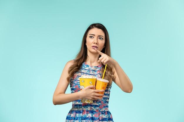Widok z przodu młoda kobieta trzyma napój popcorn i ogląda film na niebieskiej powierzchni