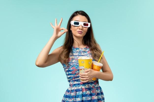 Widok z przodu młoda kobieta trzyma napój popcorn w d okulary przeciwsłoneczne na jasnoniebieskiej powierzchni