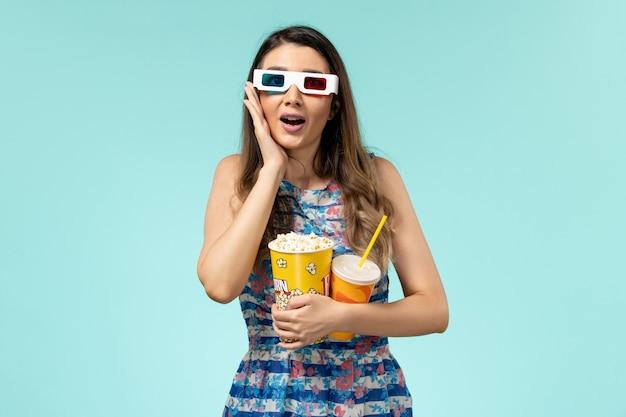 Widok z przodu młoda kobieta trzyma napój popcorn w d okulary przeciwsłoneczne na niebieskiej powierzchni