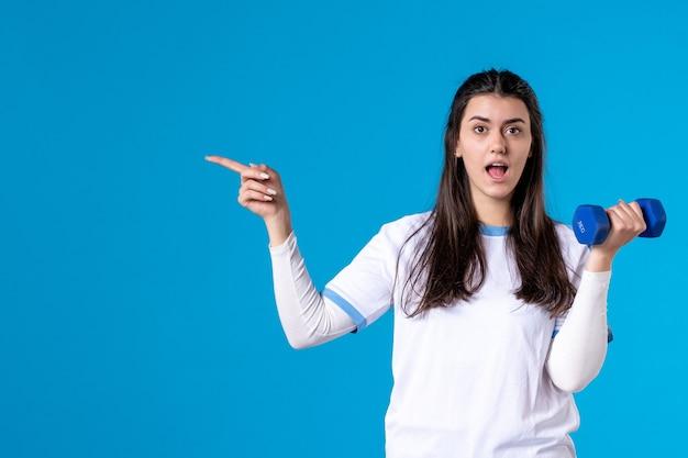 Widok z przodu młoda kobieta trzyma niebieski hantle